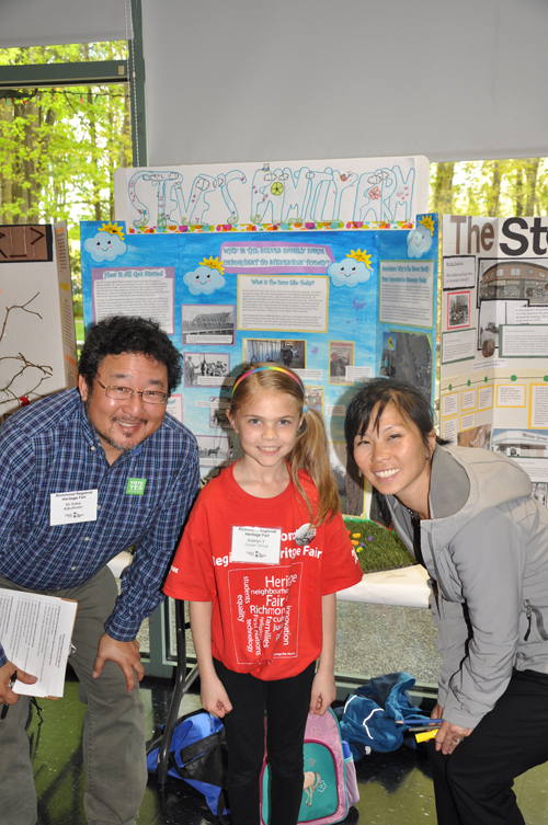 Girl poses in front of Heritage Fair project about Steves Family Farm between two judges, one male on the left and one female on the right.