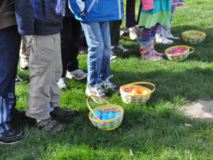 Children line up behind baskets of eggs on a grassy field during Food for Thought field trip to London Heritage Farm.