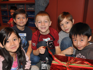 Children gathered around a present smiling for the camera during Let's Celebrate Winter field trip to Richmond Museum