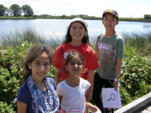 Four children smiling while posing in front of the river.