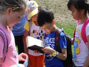 A group of children looking at a book that a boy is holding.