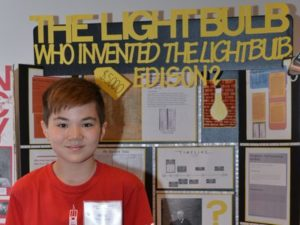 Boy in front of Heritage Fair project about the lightbulb.