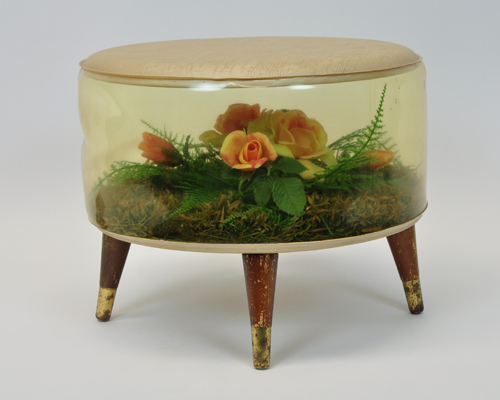 Round four legged footstool with false flower décor within